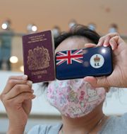 Kvinna håller upp ett pass i ett köpcenter i Hongkong.  Kin Cheung / TT NYHETSBYRÅN