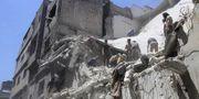Människor inspekterar en byggnad efter en bombning 27 maj.  TT