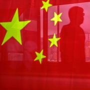A pedestrian is seen through a Chinese flag ahead of the anniversary of Hong Kong's return to Chinese in Hong Kong, China, on Wednesday, June 30, 2021. Lam Yik/Bloomberg