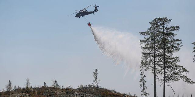 Försvarets helikopter hämtar vatten i en sjö för att vattenbomba en skogsbrand norr om Tjällmo. Jeppe Gustafsson/TT / TT NYHETSBYRÅN