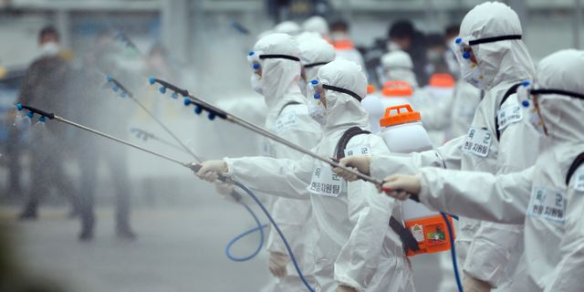 Militärer klädda i skyddsdräkter sprejar desinfektionsmedel på en tågstation i Daegu. Kim Hyun-tai / TT NYHETSBYRÅN