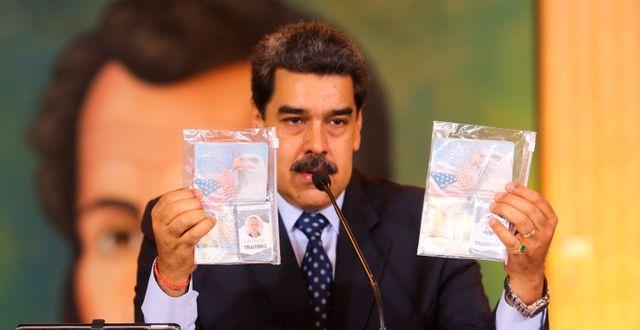 Nicolas Maduro visar upp vad han hävdar är id-kort från de två amerikanska ex-soldaterna.  TT NYHETSBYRÅN