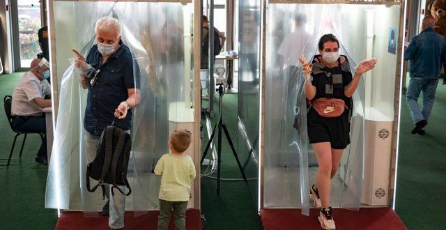 Människor går igenom ett desinfektionstält i en shoppinggalleria i Moskva.  Alexander Zemlianichenko / TT NYHETSBYRÅN