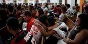 Två kvinnor iklädda Flamengo-kläder kramas under en mässa till minne av offren. Leo Correa / TT NYHETSBYRÅN/ NTB Scanpix