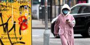 Kvinna med skyddsmask i Storbritannien. Peter Morrison / TT NYHETSBYRÅN