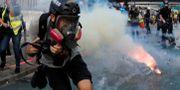 En fotograf undviker tårgas i Hongkong.  TYRONE SIU / TT NYHETSBYRÅN