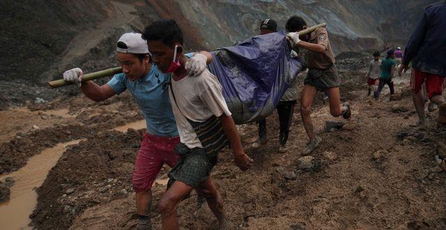 Räddningsarbetare transporterar döda kroppar efter olyckan. Zaw Moe Htet / TT NYHETSBYRÅN