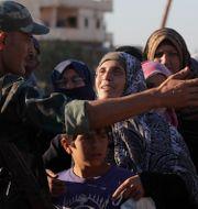 En kvinna talar med en soldat från den syriska armen i staden Rastan i samband med att hjälp distribueras. Sergei Grits / TT NYHETSBYRÅN