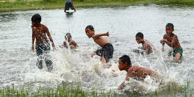 Barn leker på en översvämmad fotbollsplan i Naypyitaw, Myanmar.  Aung Shine Oo / TT / NTB Scanpix