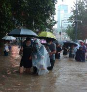 Folk vadar fram i staden Zhengzhou.  TT NYHETSBYRÅN