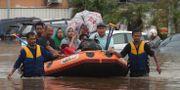 Människor evakueras med gummibåt. Achmad Ibrahim / TT NYHETSBYRÅN