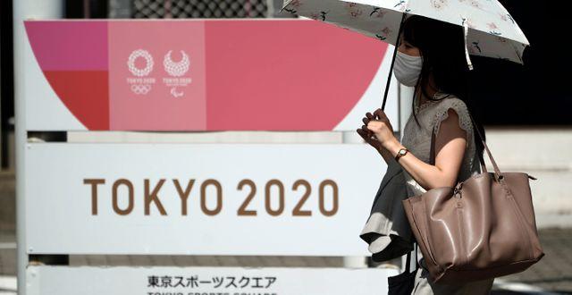 En nytagen bild på en kvinna framför en OS-skylt i Tokyo. Eugene Hoshiko / TT NYHETSBYRÅN