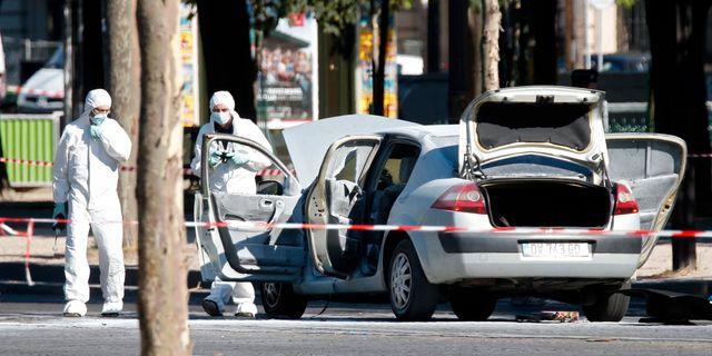 Poliser undersöker den bil som 31-åringen använde vid attentatsförsöket. CHARLES PLATIAU / TT NYHETSBYRÅN