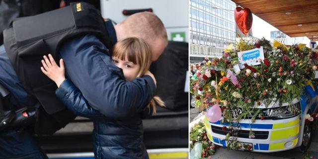 Ett barn kramar om en polis vid Sergels torg där många samlades för att hedra offren efter terrorattacken i Stockholm. TT