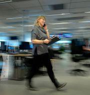 Stress i arbetslivet. En kvinna går genom ett kontorslandskap och pratar i sin telefon. Janerik Henriksson/TT / TT NYHETSBYRÅN