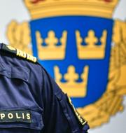 Polis och en skylt från Skattemyndigheten.  TT