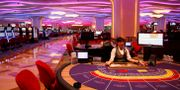 En croupier sitter vid ett baccaratbord i ett av Macaos – numera helt folktomma – kasinon.  Kin Cheung / TT NYHETSBYRÅN