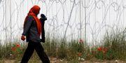 Arkivbild. En kvinna går ett staket vid Ungerns gräns. Darko Vojinovic / TT / NTB Scanpix