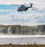 Försvarsmaktens helikopter fyller på sin brandtunna.  Johan Nilsson/TT / TT NYHETSBYRÅN
