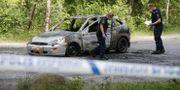 Polisen undersöker den utbrända bilen Fredrik Persson/TT / TT NYHETSBYRÅN