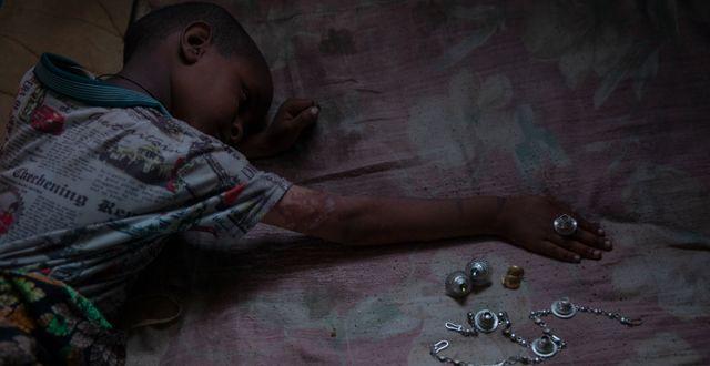 Femårige Micheale Gebremariam leker med smycken som tillhörde hans nu avlidna mamma Letay. Den kvarvarande familjen befinner sig nu i ett flyktingläger i Hamdayet i östra Sudan. Nariman El-Mofty / TT NYHETSBYRÅN