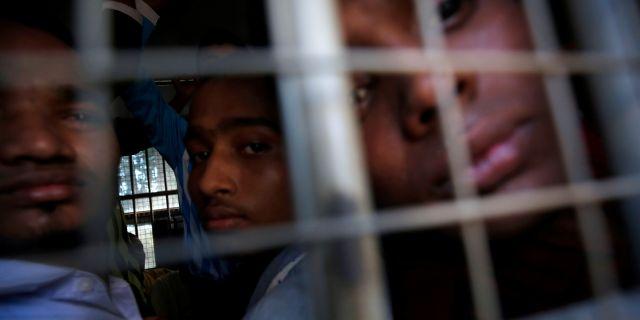 Män tillhörande folkgruppen rohingyer blickar ut från en polisbil efter att ha blivit anklagade för att resa utan rätt dokument.  ANN WANG / TT NYHETSBYRÅN