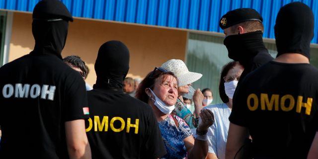 En kvinna argumenterar med poliser som blockerar vägen för en grupp demonstranter i Slutsk, Belarus.  Sergei Grits / TT NYHETSBYRÅN