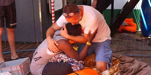 En migrant tröstas av en av Open Arms besättningsmedlemmar. Francisco Gentico / TT NYHETSBYRÅN/ NTB Scanpix