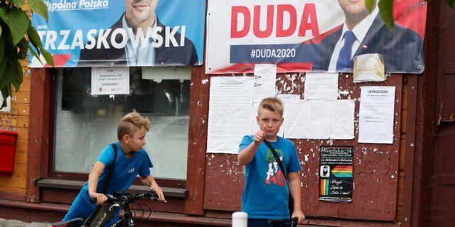 Barn som leker under affischer med de bägge kandidaterna.  Czarek Sokolowski / TT NYHETSBYRÅN
