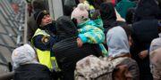 En polis försöker muntra upp en liten flicka i kön av ankommande flyktingar vid Hyllie station utanför Malmö i november 2015.  Johan Nilsson/TT / TT NYHETSBYRÅN