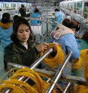 Kinesisk arbetare i en fabrik.  TT NYHETSBYRÅN