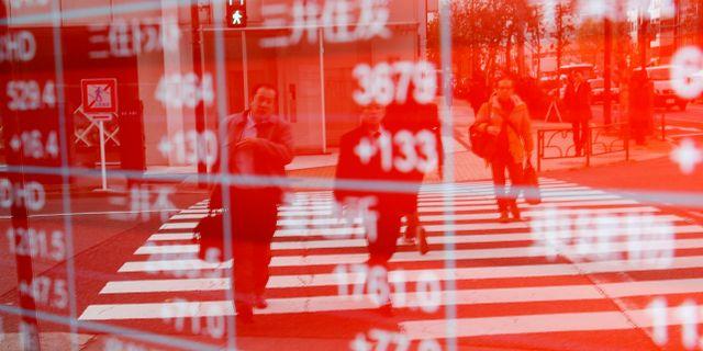 Fotgängare reflekteras mot en tavla som visar börskurser i Tokyo d7d559ef615ed