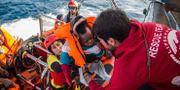 Ett barn lyfts över till en spansk räddningsbåt efter att ha räddats utanför Libyens kust.  Olmo Calvo / TT NYHETSBYRÅN