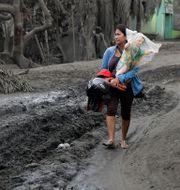 En kvinna tar med sig några ägodelar inför evakueringen.  Aaron Favila / TT NYHETSBYRÅN