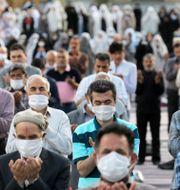 Människor ber med ansiktsmask och handskar. Ebrahim Noroozi / TT NYHETSBYRÅN