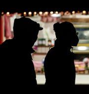 Två personer med munskydd passerar en julmarknad i storstaden Düsseldorf under julfirandet. Martin Meissner / TT NYHETSBYRÅN