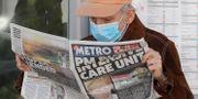 En man läser en tidning med Boris Johnson på framsidan.  Kirsty Wigglesworth / TT NYHETSBYRÅN