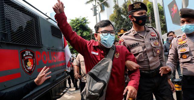 En demonstrant leds iväg av polis. Tatan Syuflana / TT NYHETSBYRÅN
