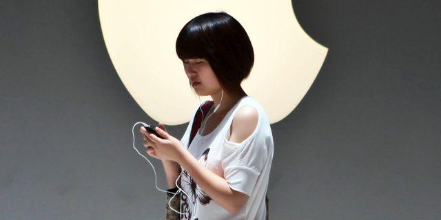 Illustrationsbild: Kinesisk kvinna utanför Apple-butik i Shanghai. TT NYHETSBYRÅN