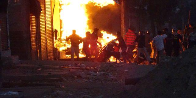En grupp demonstranter sätter eld på en affär. TT NYHETSBYRÅN