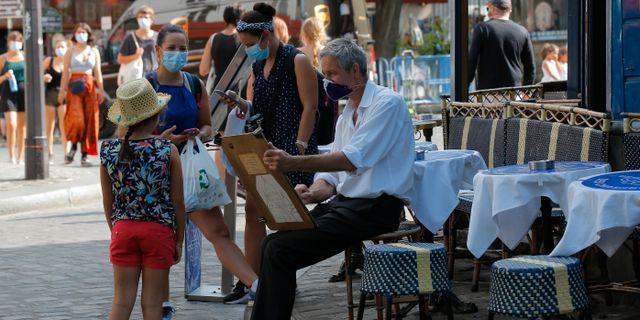En flicka får sitt porträtt målat i Montmartre i Paris tidigare i veckan.  Michel Euler / TT NYHETSBYRÅN