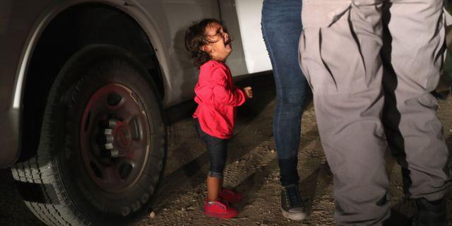 En tvåårig flicka från Honduras gråter medan hennes mamma grips av gränsvakter vid gränsen mellan USA och Mexiko, 12 juni 2018. JOHN MOORE / GETTY IMAGES NORTH AMERICA