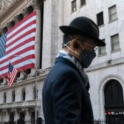 In this Nov. 16, 2020 file photo a man wearing a mask passes the New York Stock Exchange in New York. Mark Lennihan / TT NYHETSBYRÅN