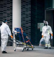 Personal iklädda skyddskläder (overaller, skyddsmask, visir) hjälper en patient sittandes på en bår in på Karolinska sjukhuset. Anders Wiklund/TT / TT NYHETSBYRÅN