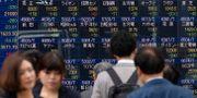 Fotgängare i Tokyo passerar tavlor med aktiekurser. KAZUHIRO NOGI / AFP