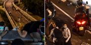Demonstranter klättrar ner från en bro och flyr i mopeder. AFP