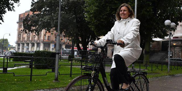 Klimat- och vice statsminister Isabella Lövin (MP) cyklar på en elcykel utanför Rosenbad i Stockholm.