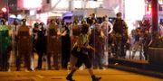 En journalist vandrar framför kravallpoliser i Hongkong. Vincent Thian / TT NYHETSBYRÅN