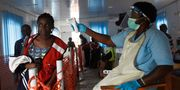 Hälsovårdspersonal tar temperaturen på en kvinna som en del av ebolascreening på gränsen mellan Kongo och Uganda. STRINGER / TT NYHETSBYRÅN