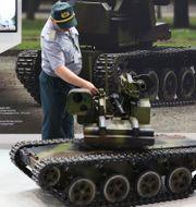 Arkivbild: En besökare på en drönarkonferens tittar på en maskingevärsbärande markgående drönare. Jon Gambrell / TT NYHETSBYRÅN